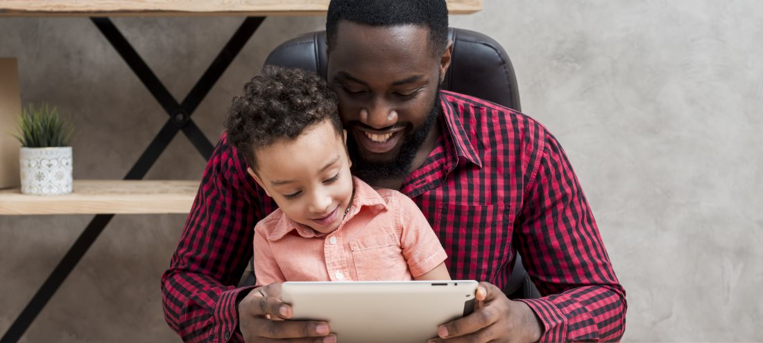 A Sandburg father has his son on his lap and they look at a tablet together