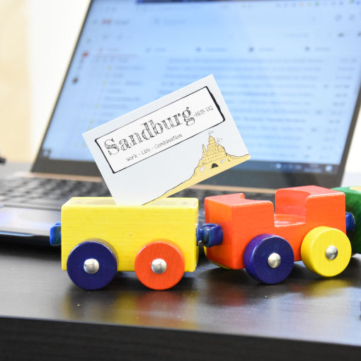A Sandburg toy train stands in front of a laptop on a desk